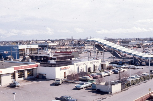 This image, looking south east toward No.3 Road in 1973, shows the Skookum Slide on the right, the back of the Richmond Savings Credit Union in the centre and Wosk's Furniture on the left. The red roof of the Dairy Queen can be seen above the Credit Union. City of Richmond Archives photo 2008 39 2 34.